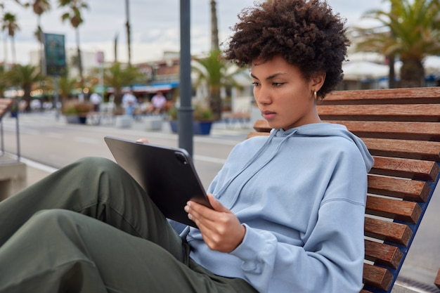 Woman tourist sits on bench in city concentrated at screen of digital tablet messages about travel vacations browses websites with touristic info thinks about web popularity