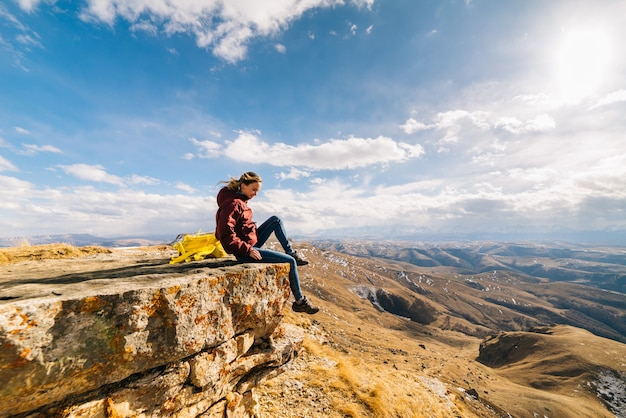 Woman tourist sits on the edge of a cliff in the background of mountains