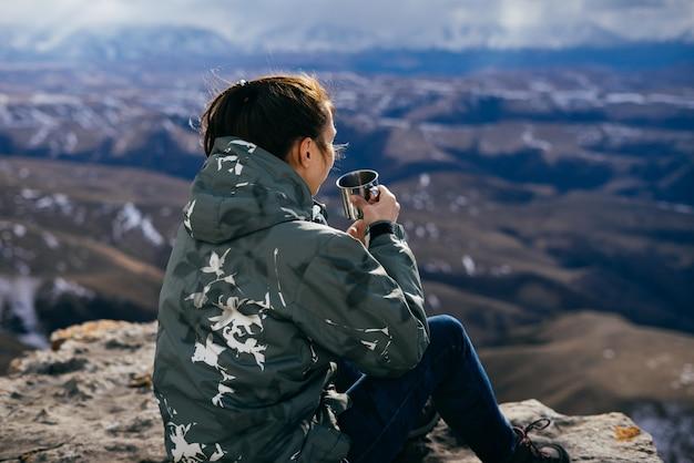 山の背景に座ってお茶を飲む女性観光客