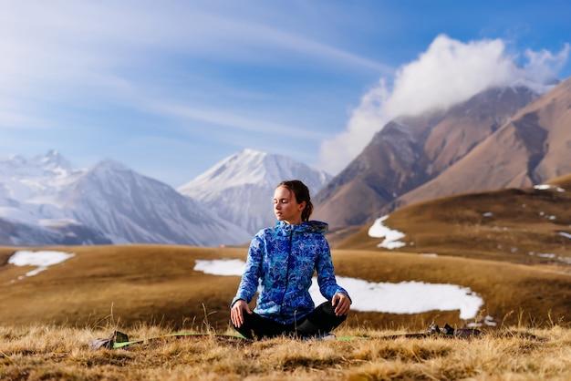 Женщина-турист сидит на фоне гор и занимается йогой