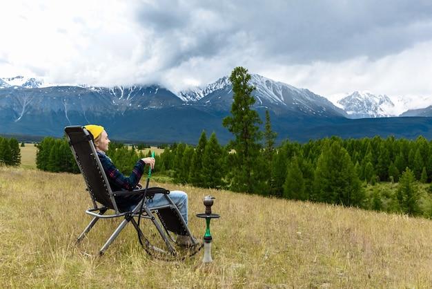 여성 관광객은 편안하게 담배를 피우며 산의 아름다운 경치를 바라보고 있습니다. 여행 및 휴식 개념