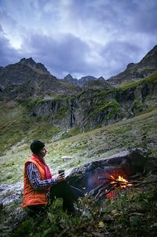 Женщина-турист сидит у костра в горах и пьет чашку кофе