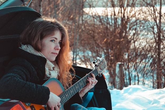 Woman tourist sitting on car and playing guitar is winter forest.