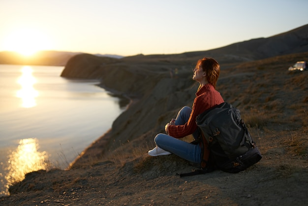 Woman tourist sitting on the ground admiring nature landscape fresh air. high quality photo