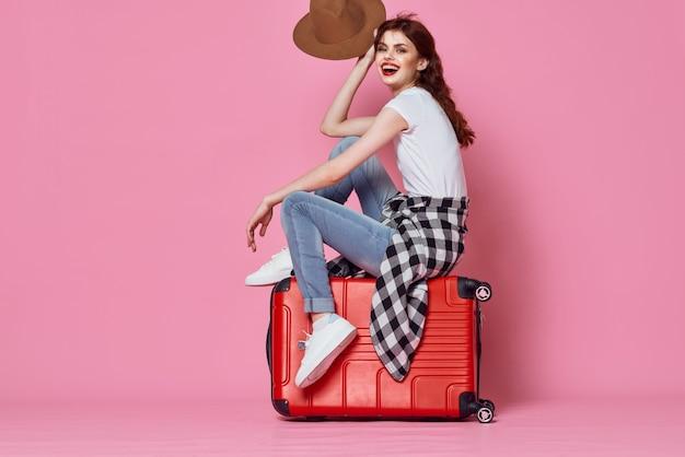 Woman tourist sitting on suitcase passenger travel destination pink background