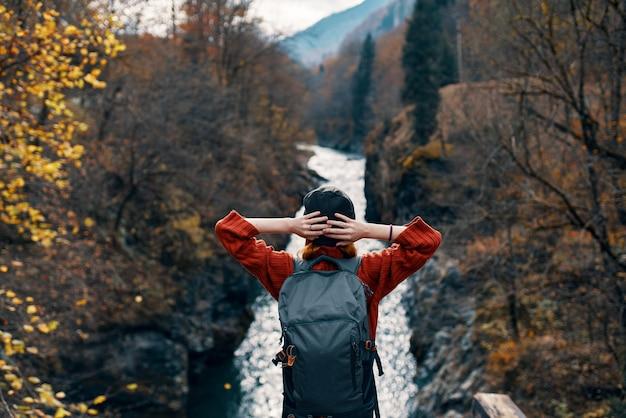 여성 관광은 강 너머 다리에 서거나 자연 경관을 존경합니다.