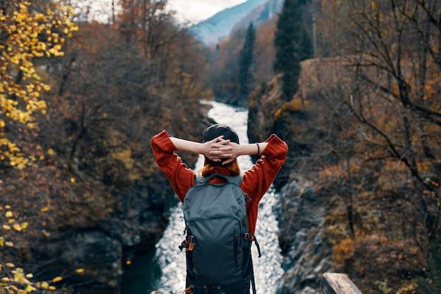 여성 관광객은 강 위에 다리에 서거나 자연 경관을 존경합니다.