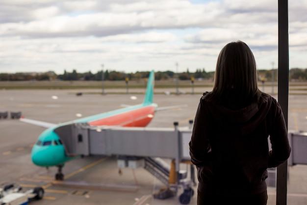 Туристическая женщина остается у окна и смотрит на самолет. ее рейс был отменен
