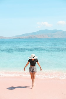Woman tourist in summer hat walking on pink sandy beach with sea view and hills at labuan bajo