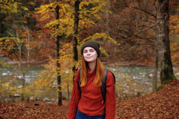 Woman tourist in a sweater hat with a backpack near tall trees in autumn in the forest