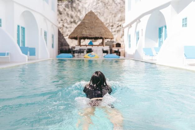여름날 수영장에서 수영하는 여성 관광객