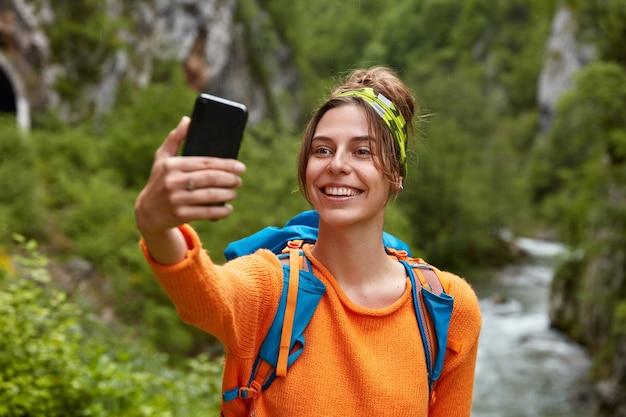 Turista donna scatta foto di se stessa con lo smart phone, ha un viaggio indimenticabile in montagna, si trova contro il ruscello