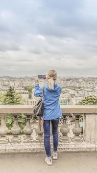 曇りの天候で都市の写真を撮る女性観光客