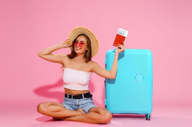 パスポートとチケットスーツケース白いトップショーツ麦わら帽子を持つ女性の観光旅行者