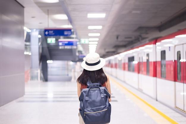 駅で電車を待っている女性観光客、旅行と休暇の概念、背面図