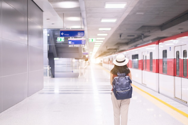 Woman tourist waiting train at train station,travel and vacation concept,back view