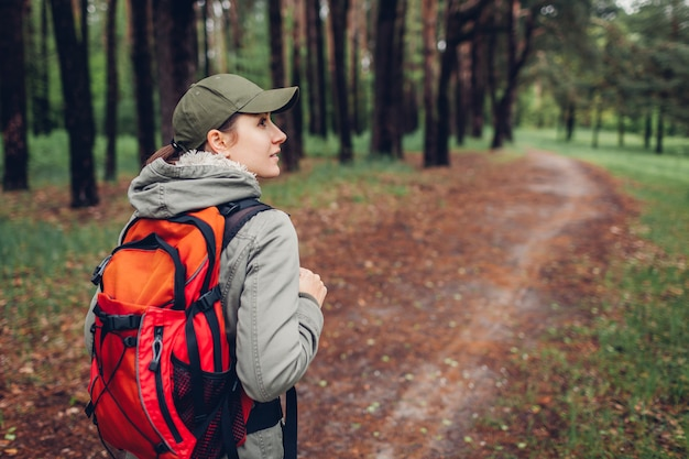 Woman tourist walking in spring forest traveling and tourism