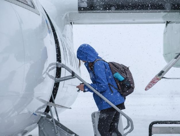 吹雪の中を飛行機に向かって歩く女性観光客