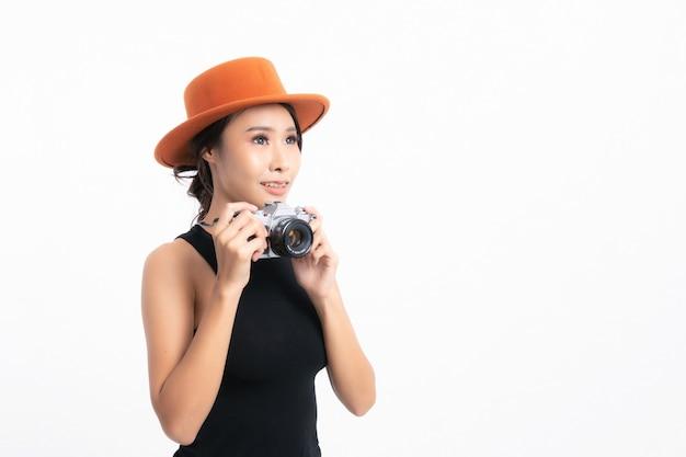 黒い帽子とジーンズのジャケットを着た女性観光客は、白い背景で隔離のスタジオショットでビンテージカメラで写真を撮るために立っています。