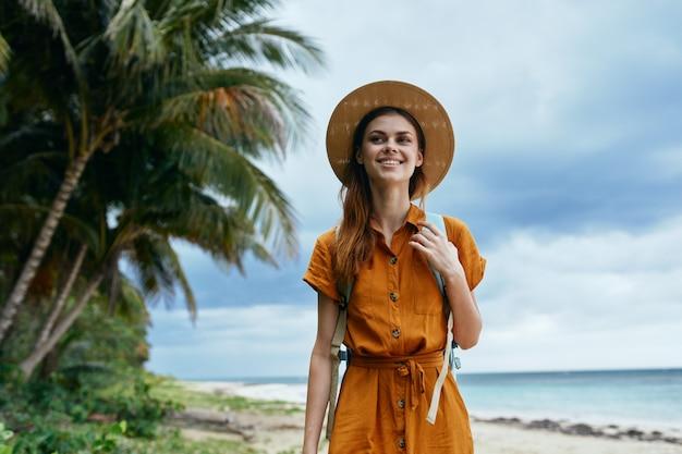 帽子をかぶった女性観光客が島のエキゾチックな旅行を歩く