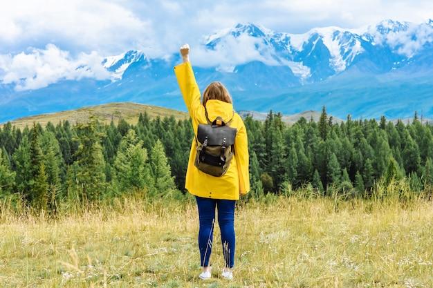 배낭을 가진 여자 관광은 정복자 포즈에서 산을 본다.