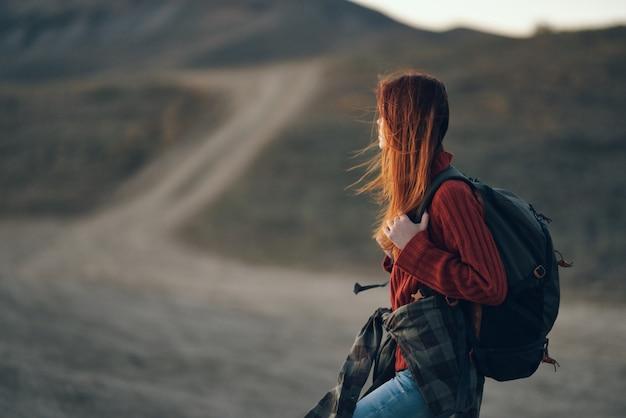 山と遠くの道で休んでいる背中にバックパックを持った女性観光客