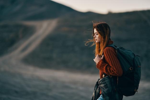 山と遠くの道で休んで背中にバックパックを持つ女性観光客