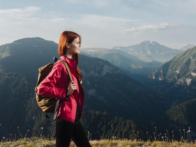 山の新鮮な空気の屋外でバックパックを持つ女性観光客