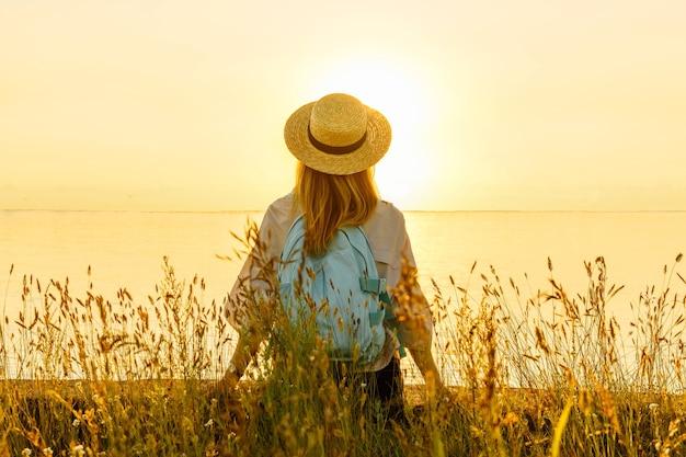 배낭을 메고 있는 여성 관광객은 해안에 앉아 해질녘 바다의 아름다운 전망을 즐깁니다. 여름 여행 및 관광 개념