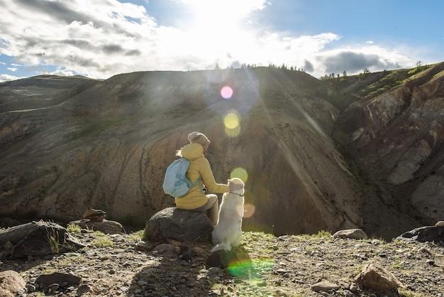 배낭을 메고 있는 여성 관광객은 개와 함께 앉아 산의 아름다운 전망을 즐깁니다. 여행 컨셉