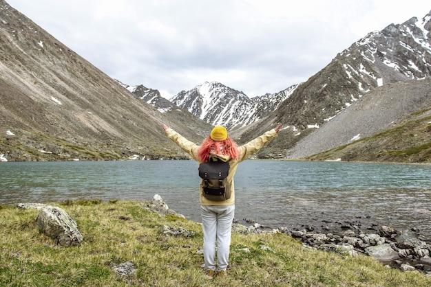 배낭을 메고 손을 든 여성 관광객은 산속에 있는 산 호수의 전망을 즐깁니다.