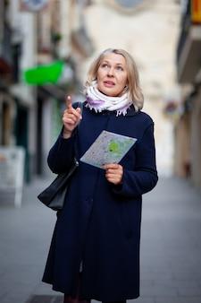 손에지도를 들고 여자 관광은 마을의 거리를 산책.