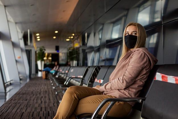マスクを口にした女性観光客がウイルスから身を守る。彼女は遠くに座って飛行機を待っていた。
