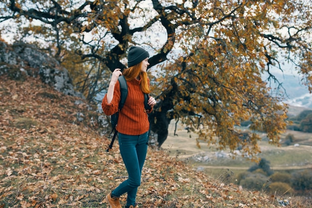 Туристическая женщина с рюкзаком в осеннем лесу путешествия природа