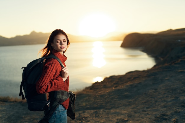 Woman tourist with backpack landscape sunset travel