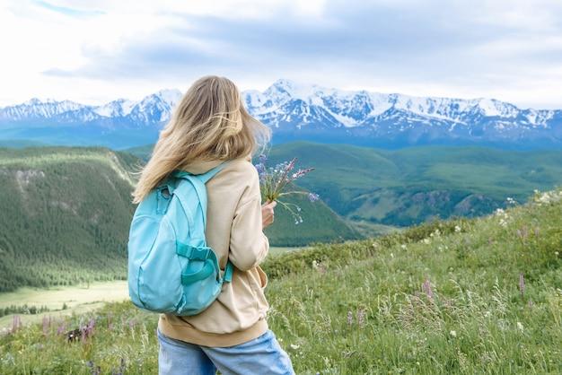 Турист женщины с рюкзаком смотрит на прекрасный вид на горы в ее поездке. концепция путешествия