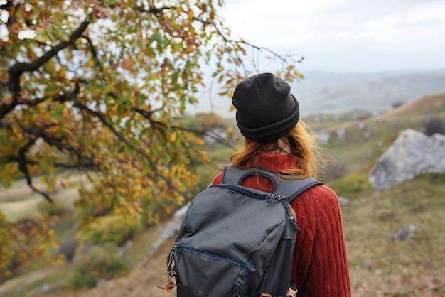 自然の風景旅行の冒険にバックパックを持つ女性の観光客