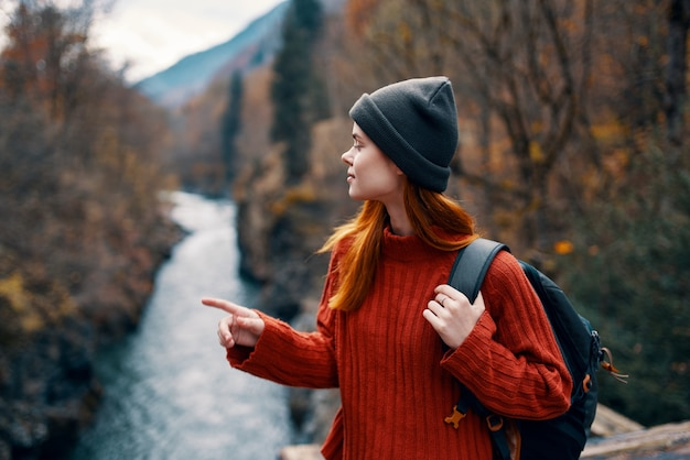 Туристическая женщина с рюкзаком на мосту у реки путешествия