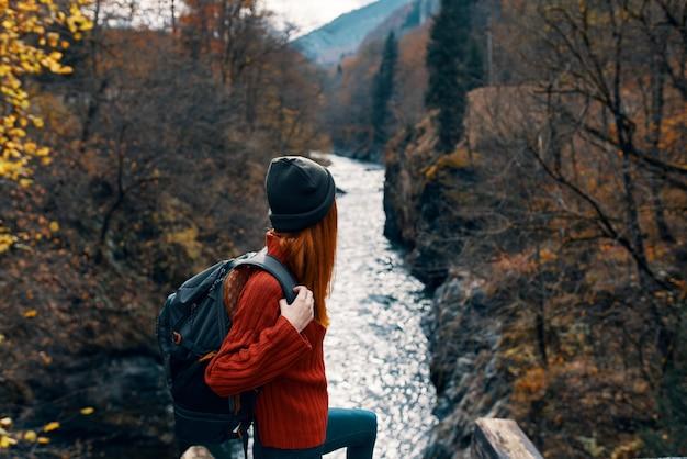 川の旅の橋の上のバックパックを持つ女性観光客