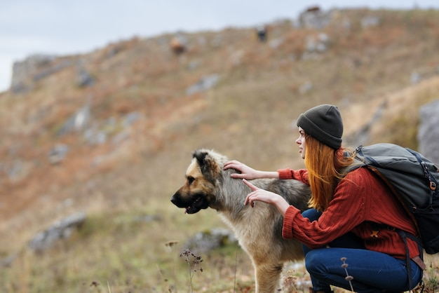 Woman tourist with backpack with dog on nature travel