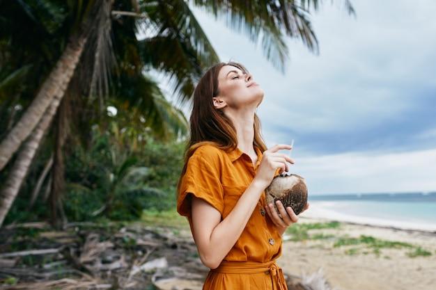 新鮮な空気の島の旅行を楽しんでいる手にココナッツカクテルを持つ女性観光客