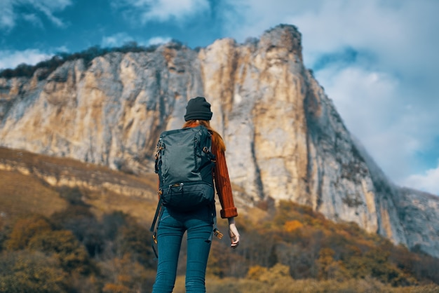 山の近くのカッターを持つ女性観光客は風景の冒険を旅行します