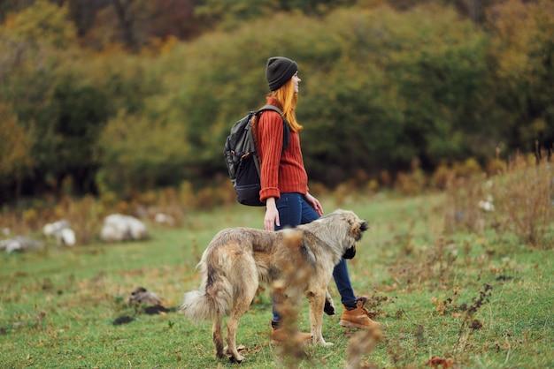 자연 여행에서 산책하는 개와 여자 관광은 모험의 자유를 전달합니다