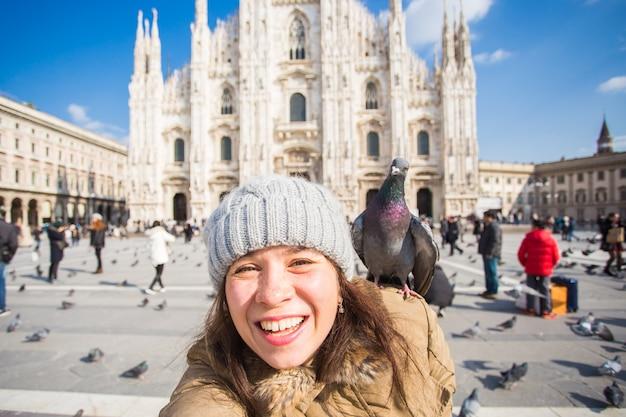 Туристка с забавными голубями делает селфи-фото перед знаменитым собором дуомо в милане.