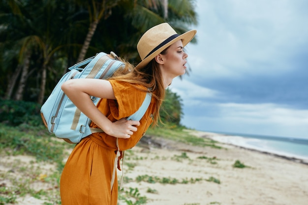 Woman tourist with heavy backpack travel to island landscape adventure walk