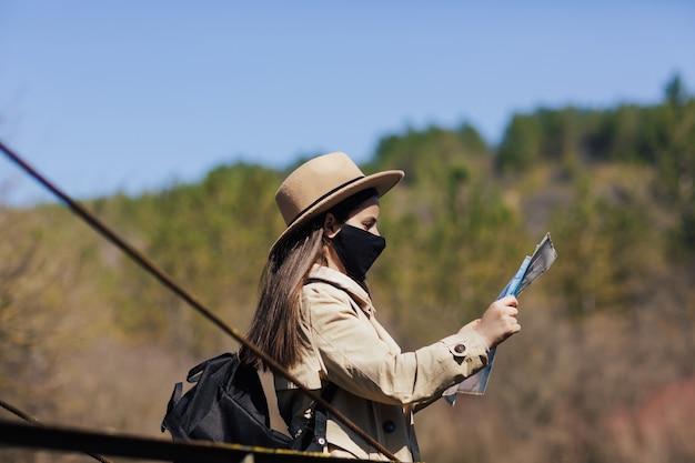 吊り橋に紙の地図と立っている保護マスクを持つ女性観光客