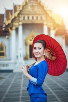 赤い伝統的な帽子を持つ女性観光