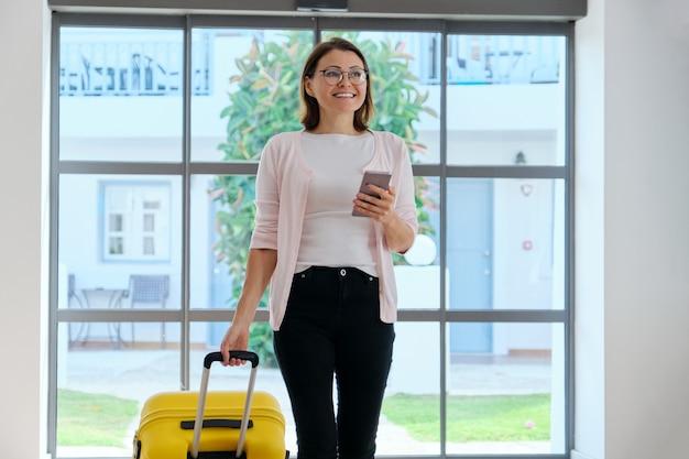 호텔 스파 리조트의 로비를 따라 걷는 여행 가방을 든 여성 관광객. 여행, 휴가, 레저, 주말, 사람들