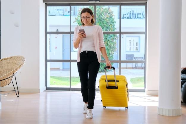 ホテルのスパリゾートのロビーに沿って歩くスーツケースを持つ女性観光客。旅行、休暇、レジャー、週末、人々