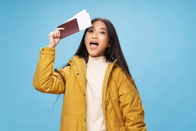 Woman tourist in yellow jacket passport and plane ticket
